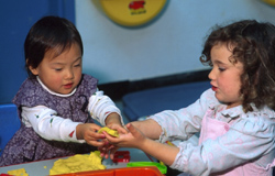 Two preschool kids playing with clay
